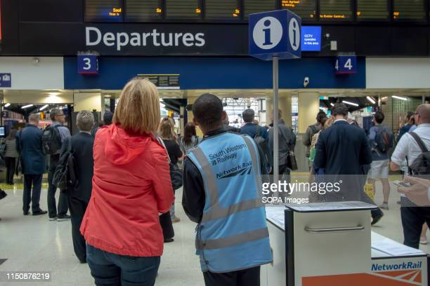 South Western Railway staff member assists the affected members of the public during the strike Industrial action taken by the National Union of Rail...