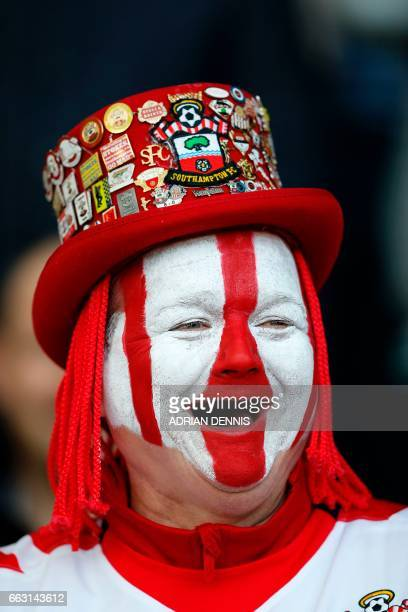 A Southampton fan with a painted face laughs in the crowd ahead of the English Premier League football match between Southampton and Bournemouth at...