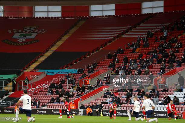 Southampton fans looks on as both teams take a knee in support of the 'Black Lives Matter' movement ahead of the Premier League match between...