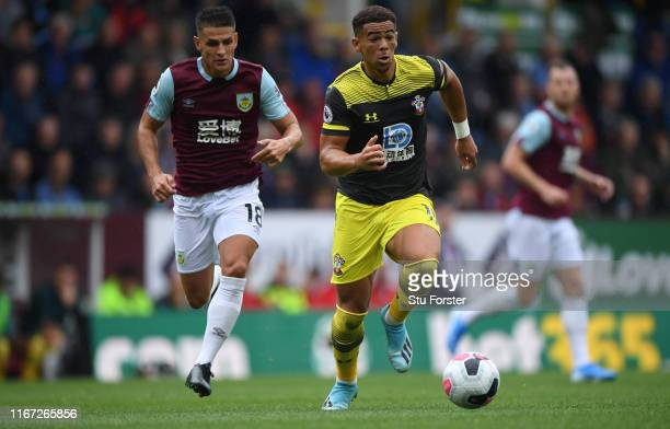 Southampton player Che Adams outpaces Ashley Westwood during the Premier League match between Burnley FC and Southampton FC at Turf Moor on August 10...