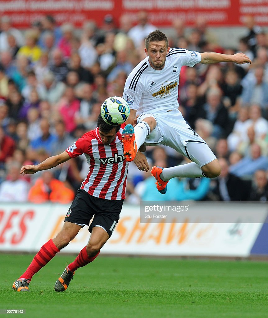 Southampton player Jack Cork (l) is beaten to the ball by Gylfi Sigurdsson of Swansea during the Barclays Premier League match between Swansea City and Southampton at Liberty Stadium on September 20, 2014 in Swansea, Wales.
