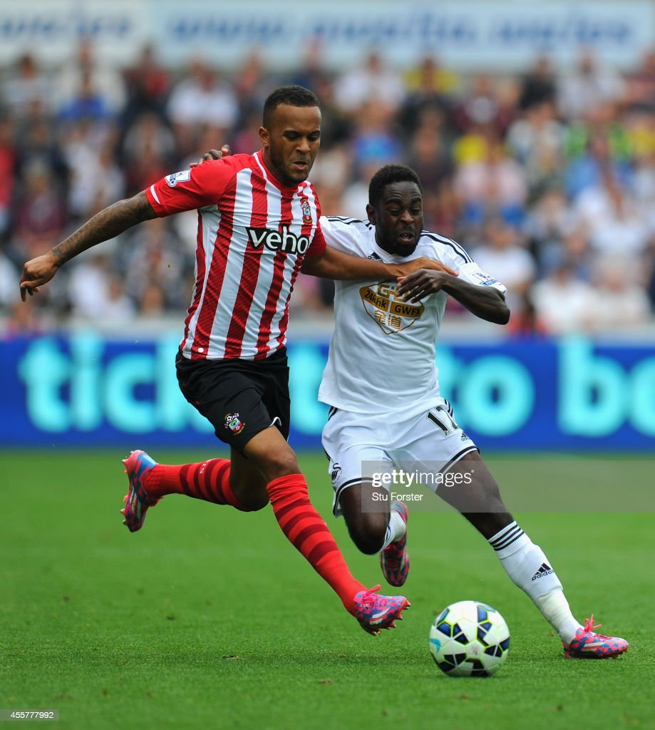 Southampton player Ryan Bertrand (l) is beaten to the ball by Nathan Dyer during the Barclays Premier League match between Swansea City and Southampton at Liberty Stadium on September 20, 2014 in Swansea, Wales.