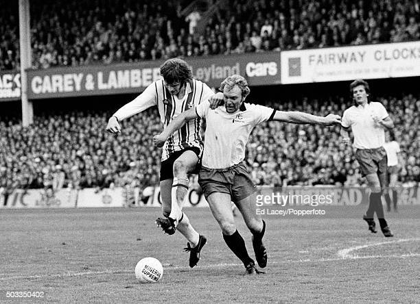 Southampton striker Mick Channon is challenged by Fulham defender Bobby Moore during their match at The Dell in Southampton, 2nd October 1976.