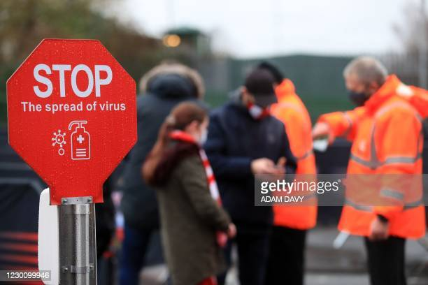 Southampton supporters wearing protective face coverings to combat the spread of the coronavirus, have their tickets checked by a steward near a hand...