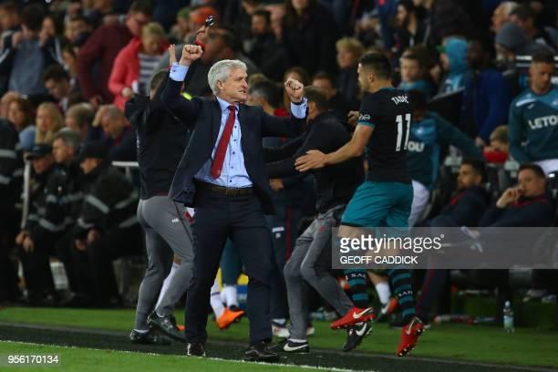 Southampton Welsh manager Mark Hughes and Southampton's Serbian midfielder Dusan Tadic react react following the English Premier League football...