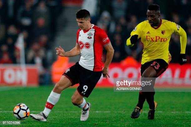 Southampton's Argentinian striker Guido Carrillo runs with the ball chased by Watford's Italian striker Stefano Okaka during the English FA Cup...