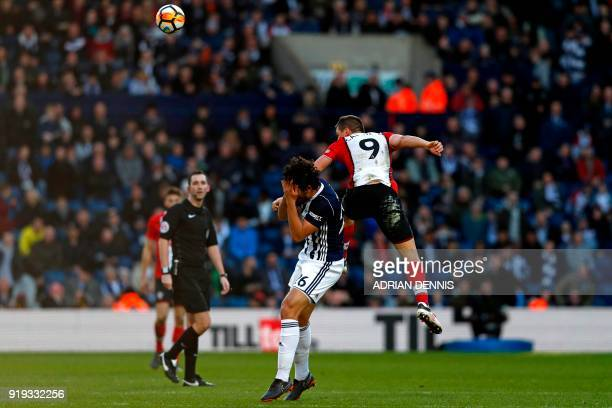 Southampton's Argentinian striker Guido Carrillo wins a header as West Bromwich Albion's Egyptian defender Ahmed Hegazy reacts to their coming...