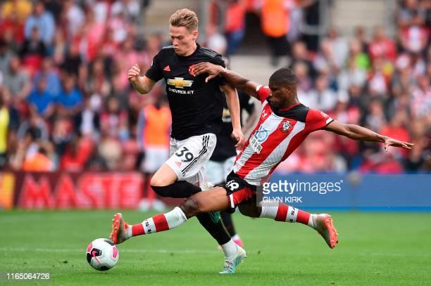 Southampton's Austrian defender Kevin Danso fouls Manchester United's English midfielder Scott McTominay to earn his second yellow card and get sent...