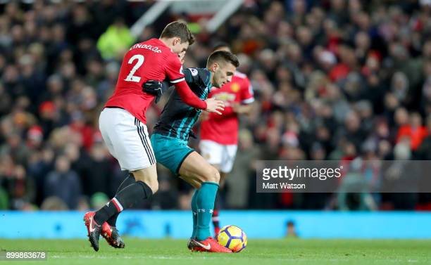 Southampton's Dusan Tadic holds off Victor Lindelof of Manchester United during the Premier League match between Manchester United and Southampton at...