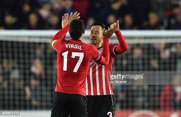 Southampton's Dutch defender Virgil van Dijk celebrates with Southampton's Japanese defender Maya Yoshida after winning the UEFA Europa League group...