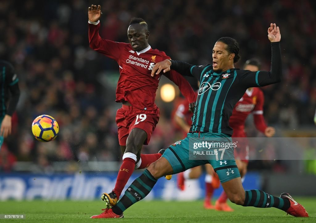Southampton's Dutch defender Virgil van Dijk (R) vies with Liverpool's Senegalese midfielder Sadio Mane during the English Premier League football match between Liverpool and Southampton at Anfield in Liverpool, north west England on November 18, 2017. / AFP PHOTO / Paul ELLIS / RESTRICTED TO EDITORIAL USE. No use with unauthorized audio, video, data, fixture lists, club/league logos or 'live' services. Online in-match use limited to 75 images, no video emulation. No use in betting, games or single club/league/player publications. /