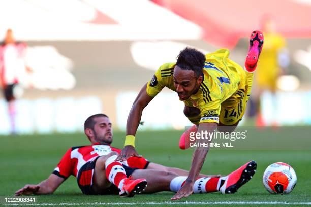 Southampton's English defender Jack Stephens tackles Arsenal's Gabonese striker PierreEmerick Aubameyang during the English Premier League football...