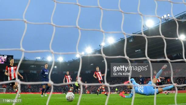 Southampton's English goalkeeper Angus Gunn dives as Tottenham Hotspur's South Korean striker Son HeungMin scores the opening goal during the English...