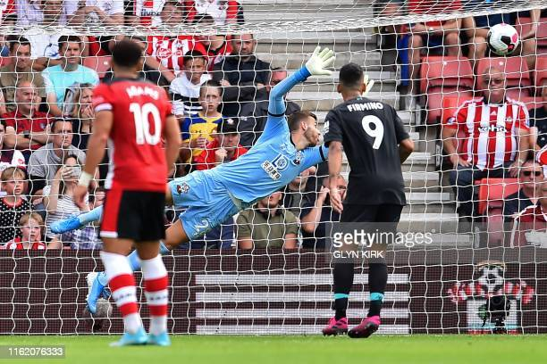 Southampton's English goalkeeper Angus Gunn dives but cannot reach the shot from Liverpool's Senegalese striker Sadio Mane as Liverpool take the lead...