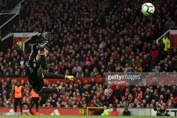 Southampton's English goalkeeper Angus Gunn dives but cannot stop Andreas Pereira's shot levelling the scores during the English Premier League...