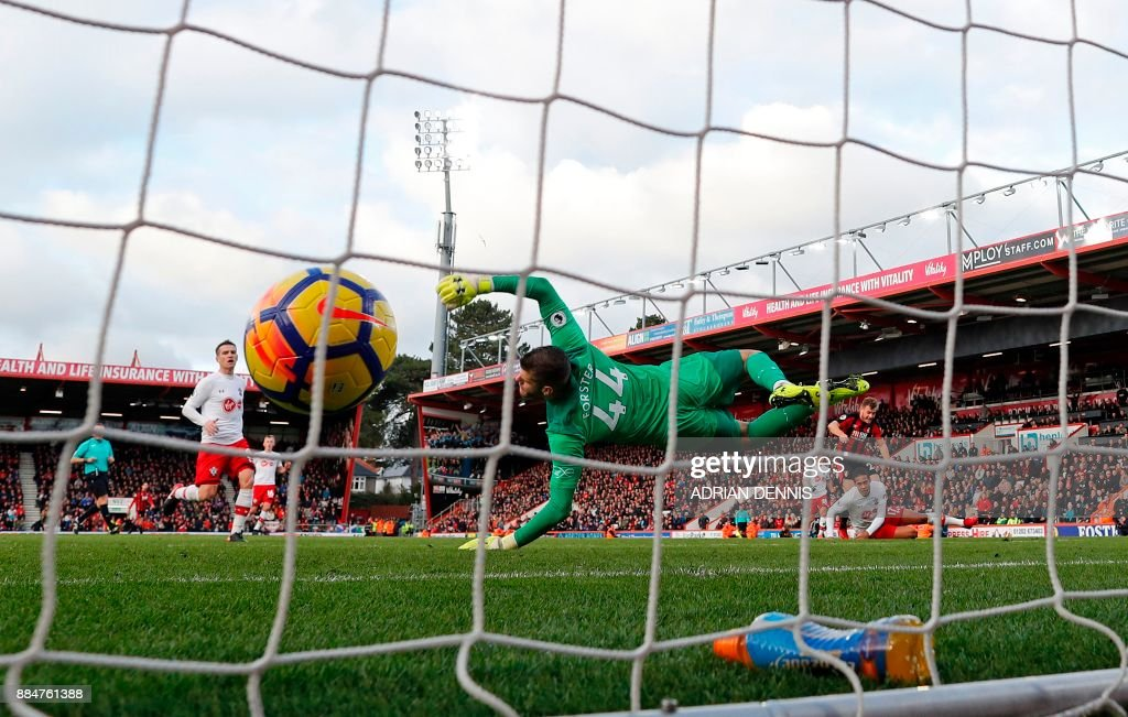 Southampton's English goalkeeper Fraser Forster (C) dives but cannot stop the shot from Bournemouth's Scottish midfielder Ryan Fraser (R) beating him for Bournemouth's first goal during the English Premier League football match between Bournemouth and Southampton at the Vitality Stadium in Bournemouth, southern England on December 3, 2017. / AFP PHOTO / Adrian DENNIS / RESTRICTED TO EDITORIAL USE. No use with unauthorized audio, video, data, fixture lists, club/league logos or 'live' services. Online in-match use limited to 75 images, no video emulation. No use in betting, games or single club/league/player publications. /