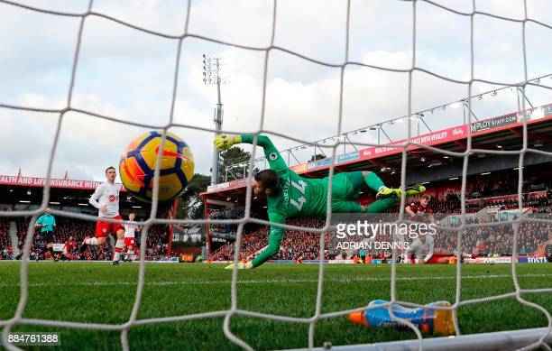 Southampton's English goalkeeper Fraser Forster dives but cannot stop the shot from Bournemouth's Scottish midfielder Ryan Fraser beating him for...