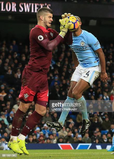 Southampton's English goalkeeper Fraser Forster saves the ball from the path of Manchester City's Belgian defender Vincent Kompany during the English...