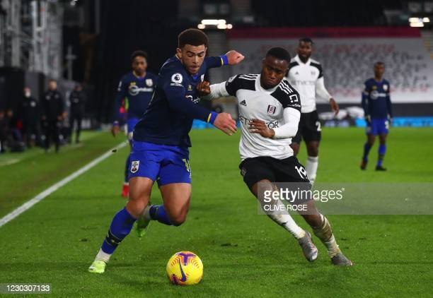 Southampton's English midfielder Che Adams fights for the ball with Fulham's English striker Ademola Lookman during the English Premier League...