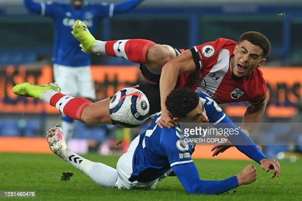 Southampton's English midfielder Che Adams goes down under a challenge from Everton's English midfielder Ben Godfrey but after a VAR review no...