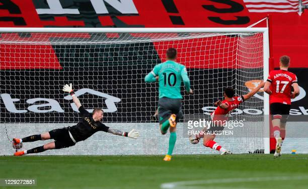 Southampton's English midfielder Che Adams shoots to the goal as Everton's English goalkeeper Jordan Pickford dives for the ball during the English...