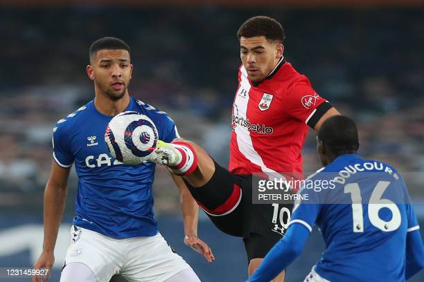 Southampton's English midfielder Che Adams vies with Everton's English defender Mason Holgate and Everton's French midfielder Abdoulaye Doucoure...