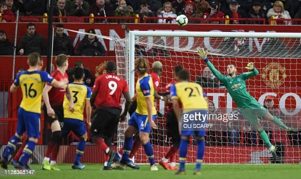 Southampton's English midfielder James WardProwse watches as his freekick beats Manchester United's Spanish goalkeeper David de Gea making the score...
