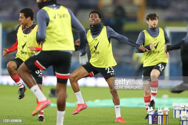 Southampton's English midfielder Nathan Tella warms up with teammates ahead of the English Premier League football match between Everton and...