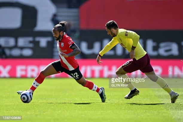 Southampton's English midfielder Theo Walcott runs with the ball as Burnley's English midfielder Dwight McNeil chases after him during the English...