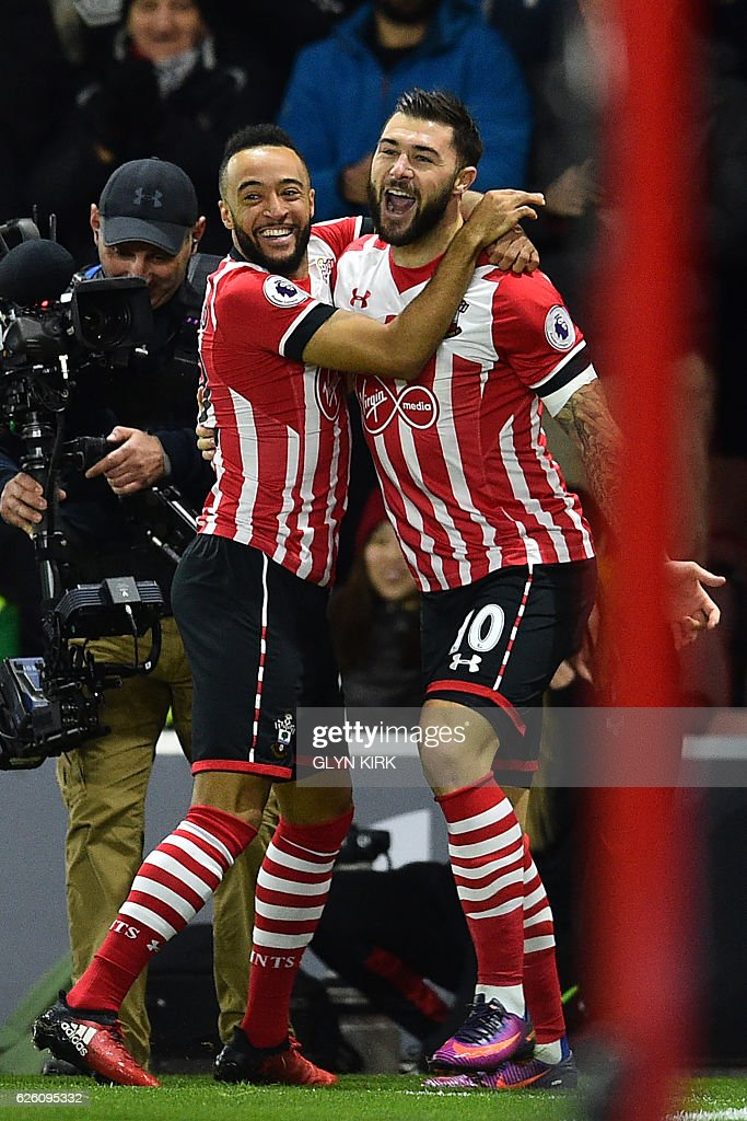 Southampton's English striker Charlie Austin (R) celebrates with Southampton's English midfielder Nathan Redmond after scoring the opening goal in the first minute of the English Premier League football match between Southampton and Everton at St Mary's Stadium in Southampton, southern England on November 27, 2016. / AFP / Glyn KIRK / RESTRICTED TO EDITORIAL USE. No use with unauthorized audio, video, data, fixture lists, club/league logos or 'live' services. Online in-match use limited to 75 images, no video emulation. No use in betting, games or single club/league/player publications. /