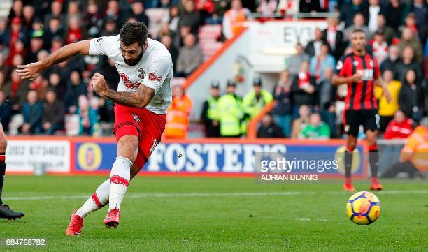 Southampton's English striker Charlie Austin shoots to score their first goal during the English Premier League football match between Bournemouth...