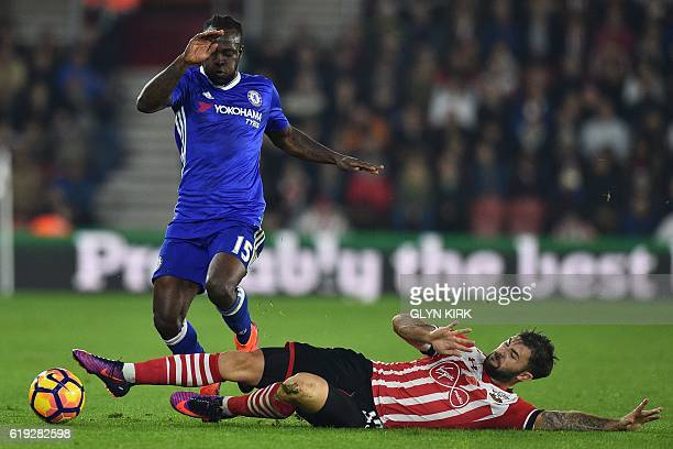 Southampton's English striker Charlie Austin tackles Chelsea's Nigerian midfielder Victor Moses during the English Premier League football match...