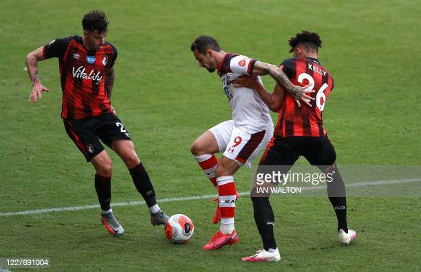 Southampton's English striker Danny Ings fights for the ball with Bournemouth's English defender Lloyd Kelly and Bournemouth's Spanish defender Diego...