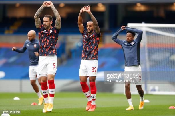 Southampton's English striker Danny Ings , Southampton's English striker Theo Walcott and Southampton's English defender Kyle Walker-Peters warm up...