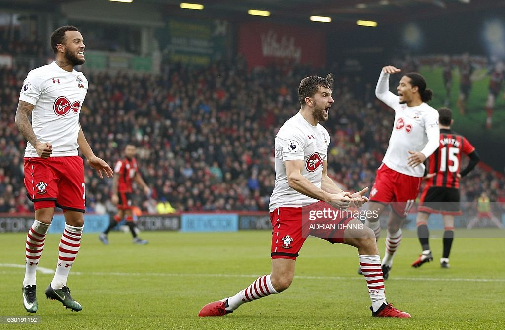 Southampton's English striker Jay Rodriguez (C) celebrates scoring his team's second goal with Southampton's English defender Ryan Bertrand (L) during the English Premier League football match between Bournemouth and Southampton at the Vitality Stadium in Bournemouth, southern England on December 18, 2016. / AFP / Adrian DENNIS / RESTRICTED TO EDITORIAL USE. No use with unauthorized audio, video, data, fixture lists, club/league logos or 'live' services. Online in-match use limited to 75 images, no video emulation. No use in betting, games or single club/league/player publications. /