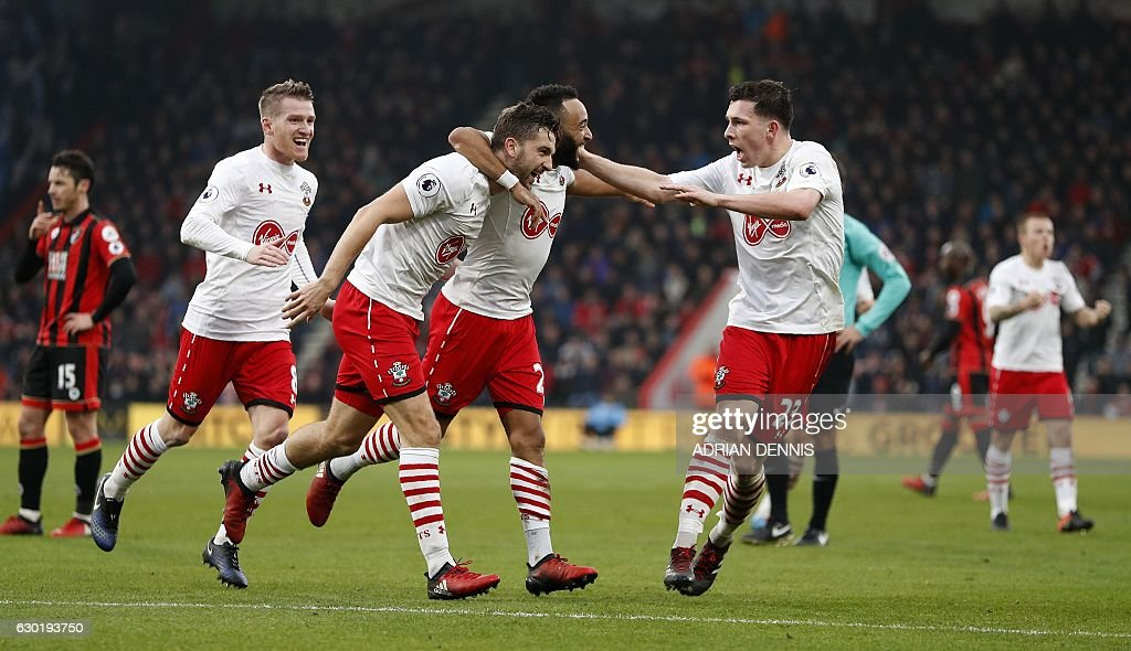 Southampton's English striker Jay Rodriguez (3L) celebrates scoring his team's third goal with Southampton's English midfielder Nathan Redmond (C) and teammates during the English Premier League football match between Bournemouth and Southampton at the Vitality Stadium in Bournemouth, southern England on December 18, 2016. / AFP / Adrian DENNIS / RESTRICTED TO EDITORIAL USE. No use with unauthorized audio, video, data, fixture lists, club/league logos or 'live' services. Online in-match use limited to 75 images, no video emulation. No use in betting, games or single club/league/player publications. /