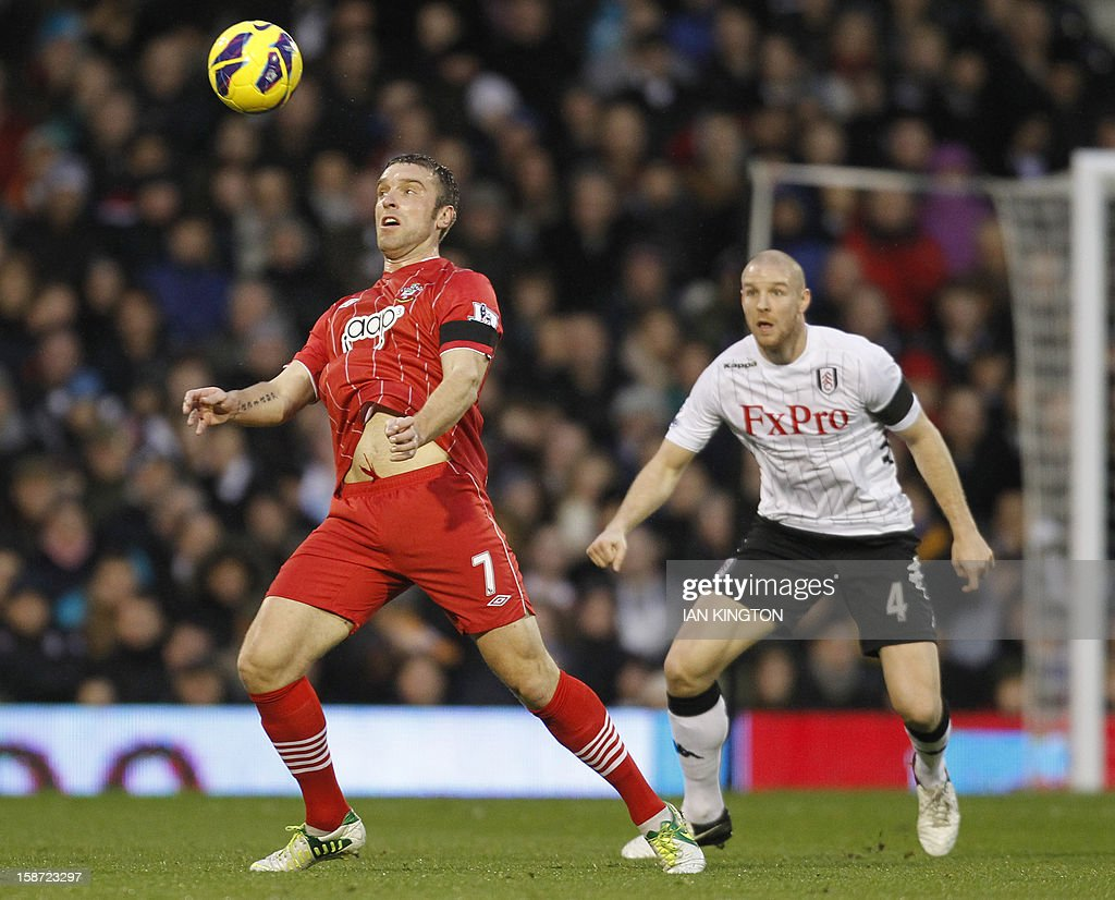 """Southampton's English striker Rickie Lambert (L) controls the ball watched by Fulham's Swiss defender Philippe Senderos (R) during the English Premier League football match between Fulham and Southampton at Craven Cottage in London, England on December 26, 2012. USE. No use with unauthorized audio, video, data, fixture lists, club/league logos or """"live"""" services. Online in-match use limited to 45 images, no video emulation. No use in betting, games or single club/league/player publications"""
