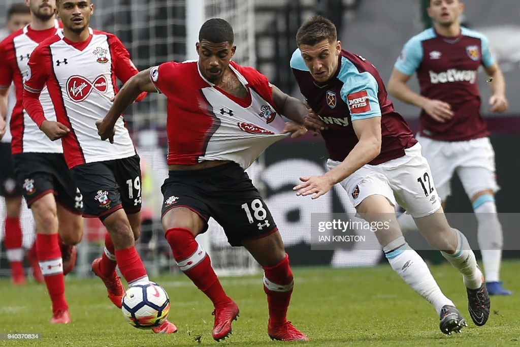 TOPSHOT - Southampton's Gabonese midfielder Mario Lemina vies with West Ham United's English striker Jordan Hugill (2nd R) during the English Premier League football match between West Ham United and Southampton at The London Stadium, in east London on March 31, 2018. / AFP PHOTO / Ian KINGTON / RESTRICTED TO EDITORIAL USE. No use with unauthorized audio, video, data, fixture lists, club/league logos or 'live' services. Online in-match use limited to 75 images, no video emulation. No use in betting, games or single club/league/player publications. /