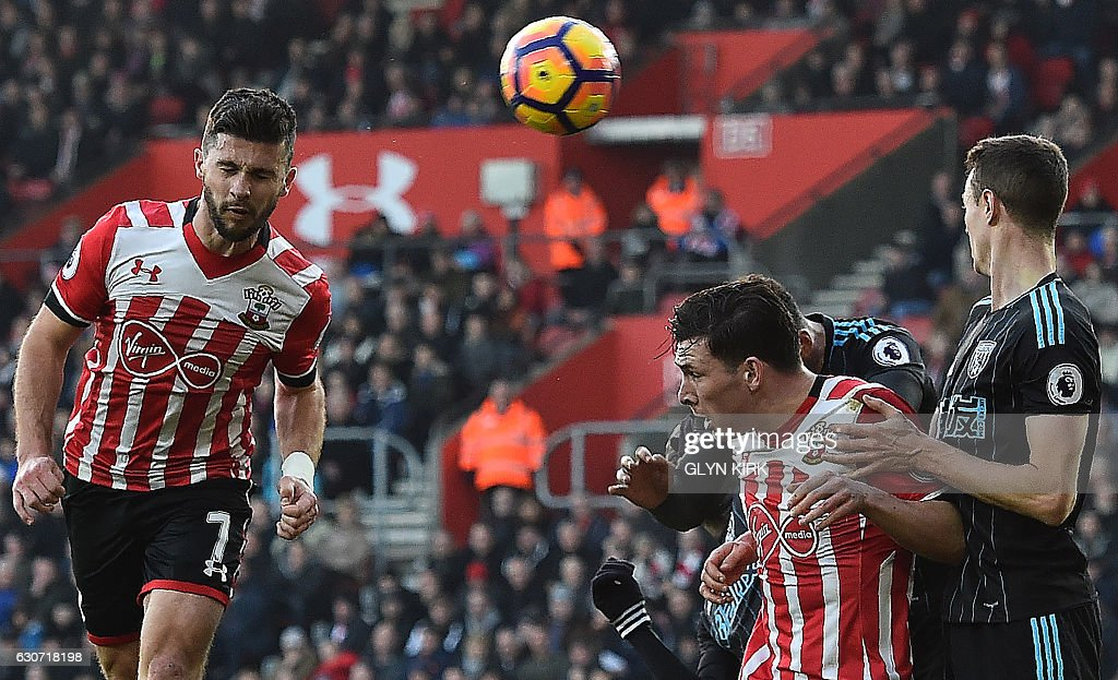 Southampton's Irish striker Shane Long (L) heads the ball to score his team's first goal during the English Premier League football match between Southampton and West Bromwich Albion at St Mary's Stadium in Southampton, southern England on December 31, 2016. / AFP / Glyn KIRK / RESTRICTED TO EDITORIAL USE. No use with unauthorized audio, video, data, fixture lists, club/league logos or 'live' services. Online in-match use limited to 75 images, no video emulation. No use in betting, games or single club/league/player publications. /