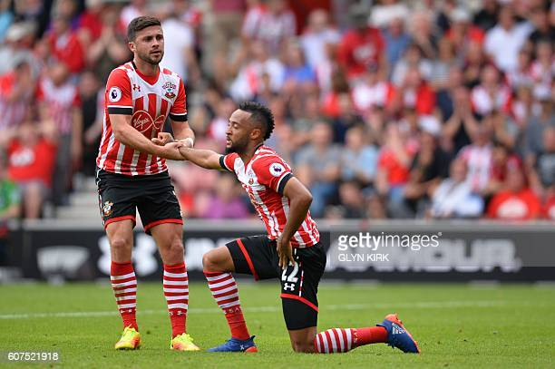 Southampton's Irish striker Shane Long helps up Southampton's English midfielder Nathan Redmond after he missed a shot on goal during the English...
