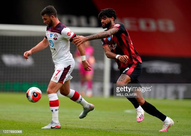 Southampton's Irish striker Shane Long is challenged by Bournemouth's Danish midfielder Philip Billing during the English Premier League football...