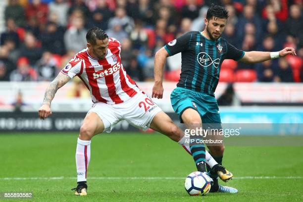 Southampton's Irish striker Shane Long vies with Stoke City's US defender Geoff Cameron during the English Premier League football match between...