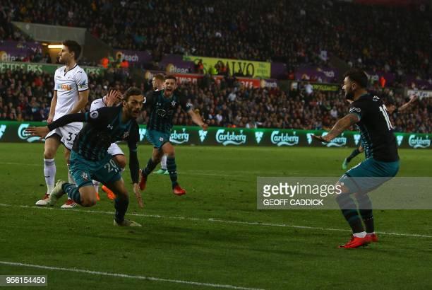 Southampton's Italian striker Manolo Gabbiadini celebrates scoring his team's first goal with Southampton's English striker Charlie Austin during the...