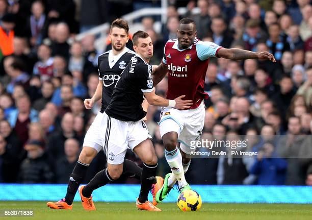 Southampton's Morgan Schneiderlin and West Ham United's Guy Demel battle for the ball