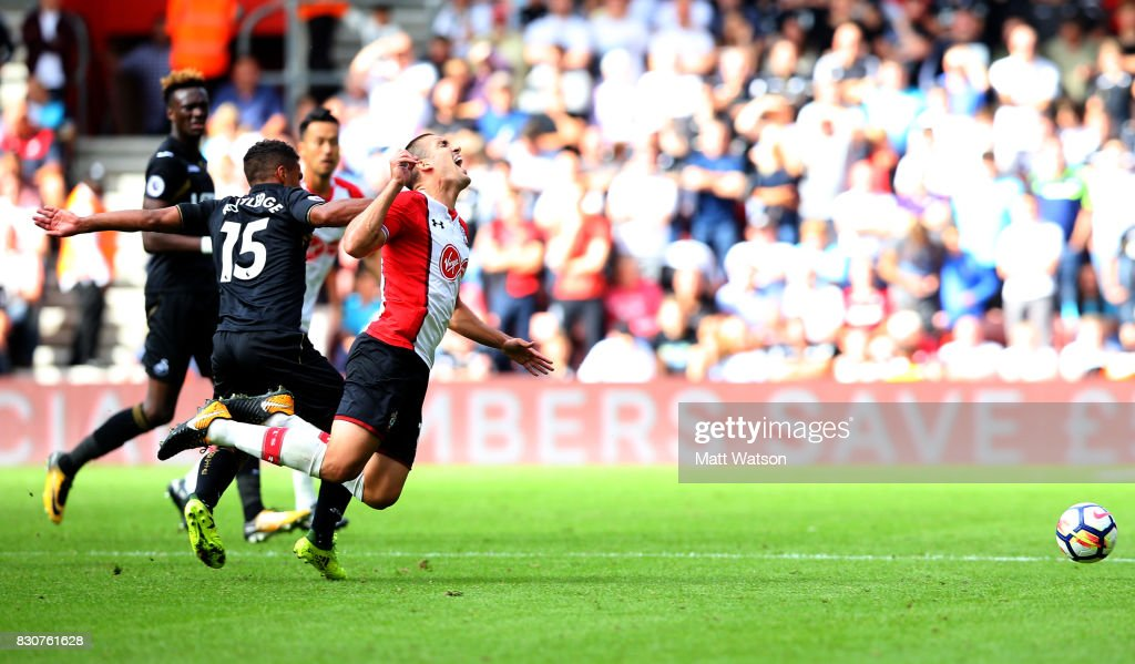 Southampton's Oriol Romeu (right) feels the affects of a tackle from Swansea City's Wayne Routledge during the Premier League match between Southampton and Swansea City at St Mary's Stadium on August 12, 2017 in Southampton, England.