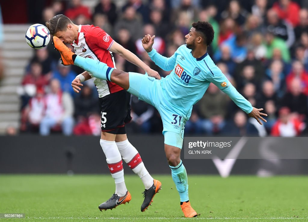 Southampton's Polish defender Jan Bednarek (L) vies with Bournemouth's French midfielder Lys Mousset during the English Premier League football match between Southampton and Bournemouth at St Mary's Stadium in Southampton, southern England on April 28, 2018. (Photo by Glyn KIRK / AFP) / RESTRICTED TO EDITORIAL USE. No use with unauthorized audio, video, data, fixture lists, club/league logos or 'live' services. Online in-match use limited to 75 images, no video emulation. No use in betting, games or single club/league/player publications. /