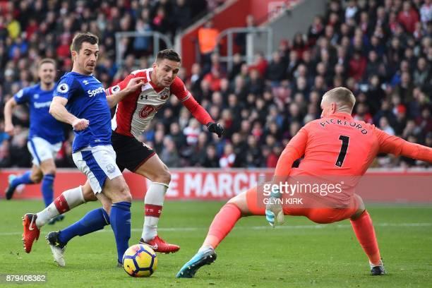 Southampton's Serbian midfielder Dusan Tadic puts the ball between Everton's English defender Leighton Baines and Everton's English goalkeeper Jordan...