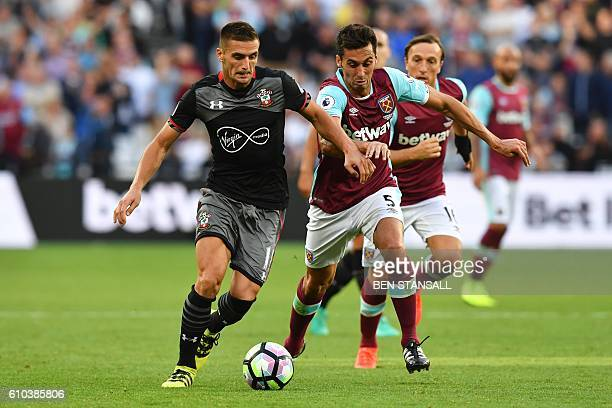 Southampton's Serbian midfielder Dusan Tadic runs with the ball chased by West Ham United's Spanish defender Alvaro Arbeloa during the English...