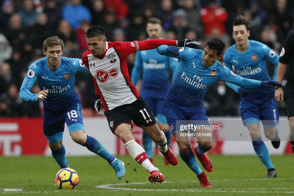 TOPSHOT - Southampton's Serbian midfielder Dusan Tadic (C) vies with Arsenal's Spanish defender Nacho Monreal (L) and Arsenal's Chilean striker Alexis Sanchez during the English Premier League football match between Southampton and Arsenal at St Mary's Stadium in Southampton, southern England on December 10, 2017. / AFP PHOTO / Adrian DENNIS / RESTRICTED TO EDITORIAL USE. No use with unauthorized audio, video, data, fixture lists, club/league logos or 'live' services. Online in-match use limited to 75 images, no video emulation. No use in betting, games or single club/league/player publications. /