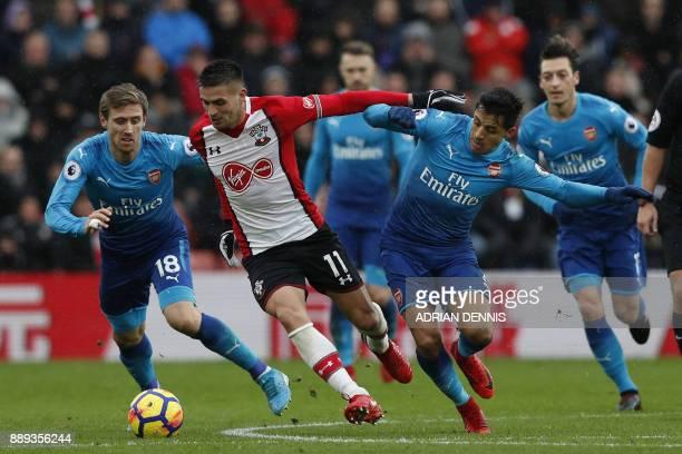 TOPSHOT Southampton's Serbian midfielder Dusan Tadic vies with Arsenal's Spanish defender Nacho Monreal and Arsenal's Chilean striker Alexis Sanchez...